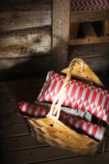 Joulusauna ja punainen väri kuuluvat jouluun. Lapuan Kankureiden Hila-saunatyyny ja laudeliina on kudottu jacquard-tekniikalla. Kuva: Lapuan Kankurit