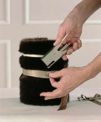 Kiedo kahta erisävyistä beigenväristä satiininauhaa kierroksen verran tiukasti astian ympärille