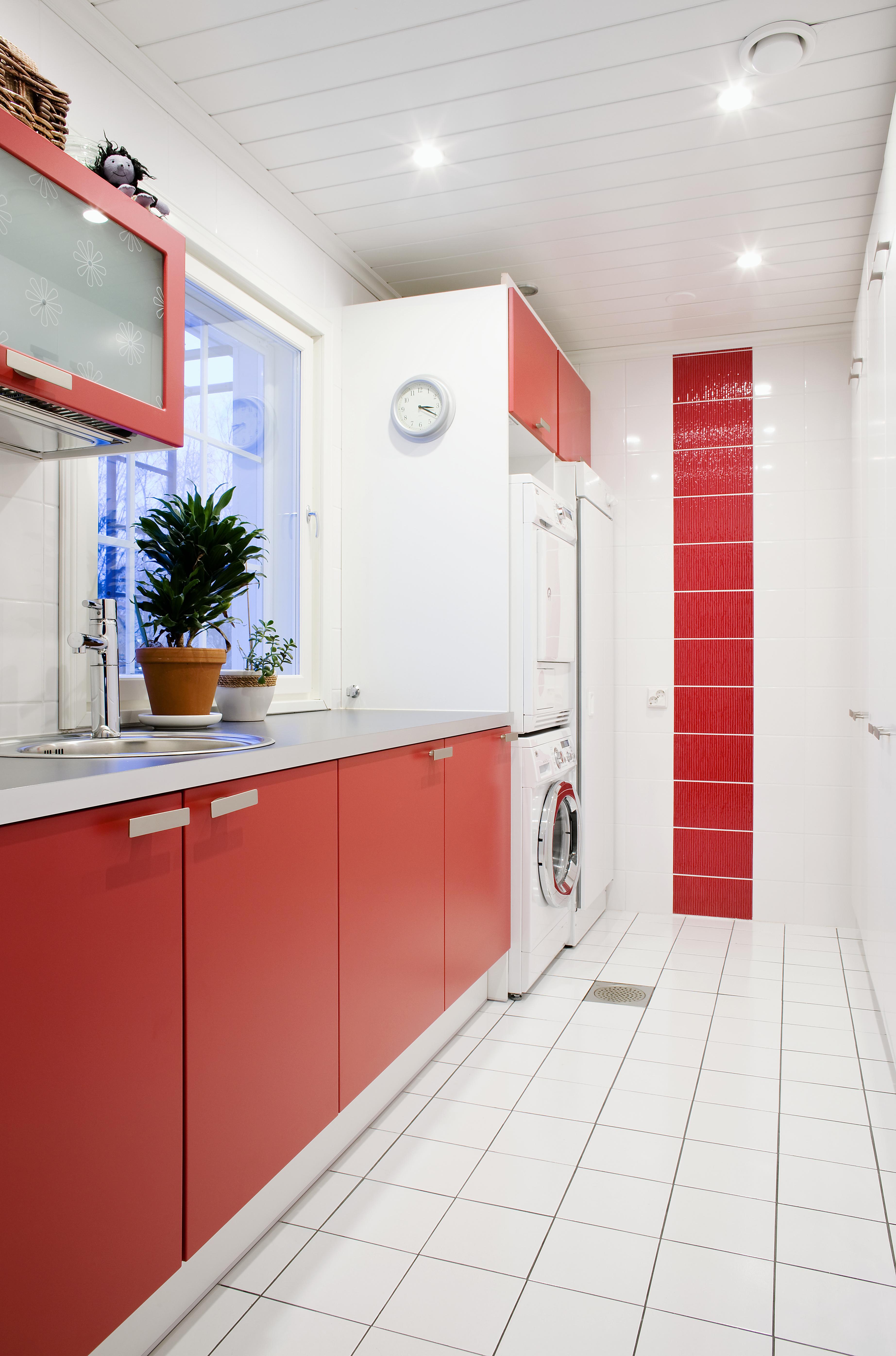 Pirteän punavalkoisen kodinhoitohuoneen toiselle seinälle on upotettu normaalisyvyyttä pienemmät säilytyskaapit. Altaan yllä tiskikaapissa on kukkakuvioinen huurrelasi. Ikkuna tuo avaruutta ja valoa. Kalusteet Puustellin.