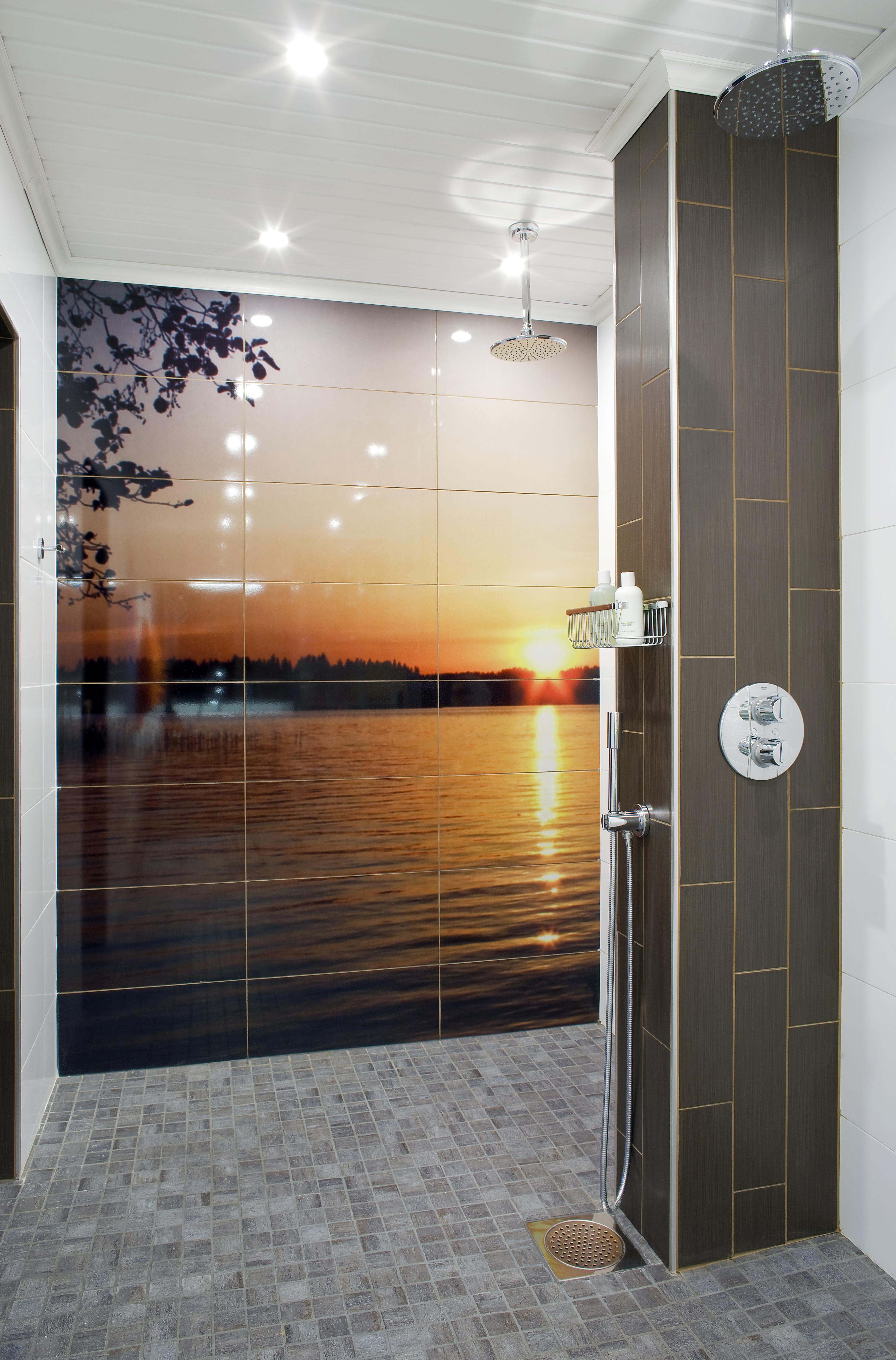 Muistoja kesämökiltä. Kylpyhuoneeseen tuo lämpöä suihkutilan upea, kaakeleihin omasta valokuvasta teetetty auringonlasku. Piiloasennetut sadesuihkut ja talon kaikki hanat ovat Grohen mallistosta.