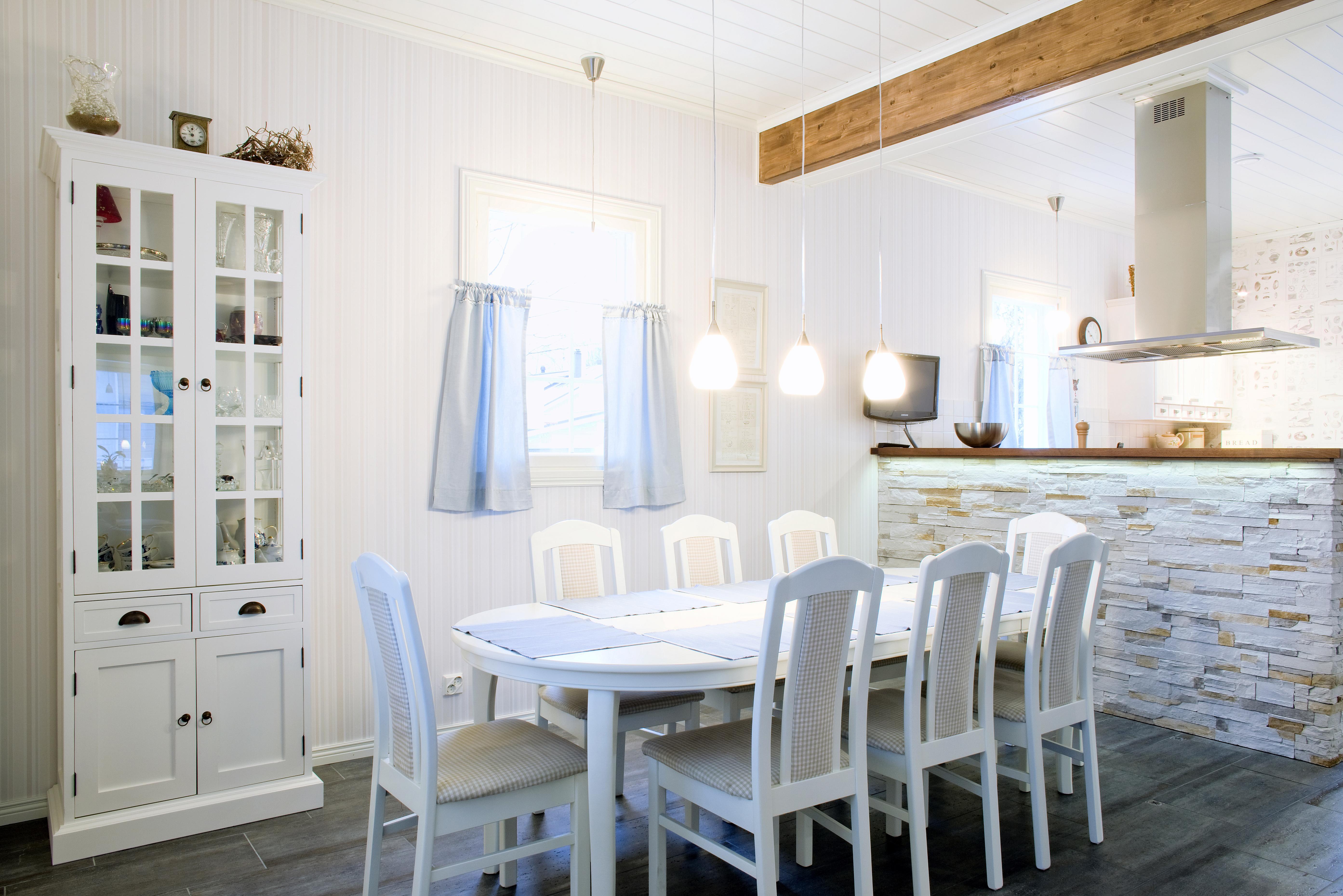 Uutta ja uudistettua. Ruokailutilan vanha, kirsikanvärinen pöytä sai uuden elämän, kun puuseppä asensi siihen jatkopalan ja maalasi sen valkoiseksi samoin kuin tuolitkin. Liesituuletin Lapetekin. Ledivalot puutason alla korostavat saarekkeen kivipintaa.