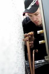 Putkimies Jukka Poikela asentaa sisäyksikön lämmitys- ja käyttövesiputket kiinni jo puolelta päivin.