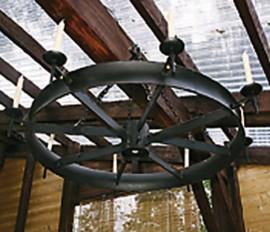 Jukka Kähönen teki kärrynpyörästä kattokruunun, joka valaisee joko kynttilöillä tai led-lampuilla.