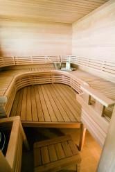 Kaarevat lauteet tuovat eloa tilavaan saunaan