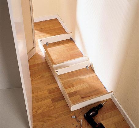 Kokoa sokkeli laudoista kulmaraudoilla ja 3,5 x 12 mm:n ruuveilla. Kiinnitä kehys lattiaan kulmaraudoilla ja 4 x 30 mm:n ruuveilla. Voit kiinnittää sokkelin myös komeroiden pohjaan, jolloin lattiaan ei tule reikiä. Kokeile, että komero seisoo suorassa - etenkin vanhassa rakennuksessa lattia tai seinä saattaa olla vino, jolloin voit auttaa asiaa höyläämällä sokkelin reunoja.