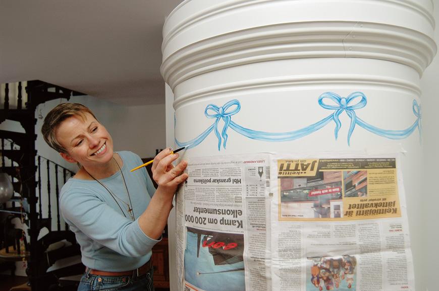 Pönttöuunin voi somistaa vaikka maalaamalla. Kuvittaja-somistaja Camilla Paro loihti uunin yläosaan rusettikranssin. Kaunis sininen väri toistuu Doddien kodissa muuallakin.