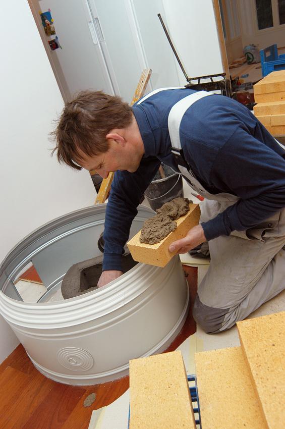 Muurari Jari Autio työssään Doddien omakotitalossa.Pönttöuuni muurataan valmiin peltirenkaan sisään. Alin rengas on upotettu parkettiin leikattuun reikään. Uunin alle ei saa jäädä palavaa materiaalia.