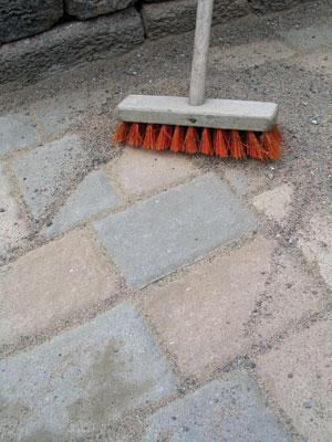 Asennuksen jälkeen harjattiin kivivälit täyteen hiekkaa. Hiekan avulla kiveyksestä tulee kuin yhtenäinen laatta.