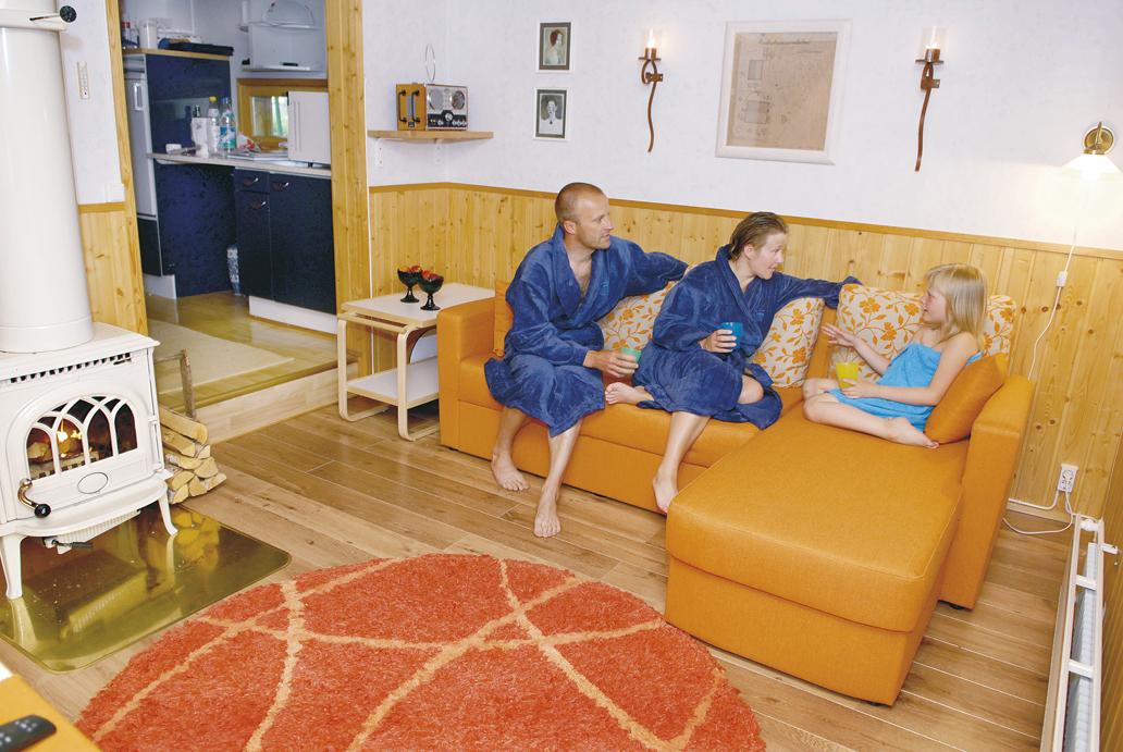 Vieras- ja takkahuoneena palvelevaan tilan asennettiin pari vuotta sitten norjalainen Jotul-takka. Pia, Marko ja Siiri nauttivat takkatulesta saunan jälkeen.