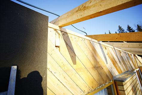 Remonttimiehet asensivat tuulensuojalevyt ja koolauslaudat vanhan umpilaudoituksen päälle talon sivustoihin ja päätyihin.