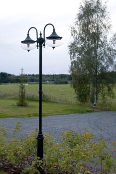 Kulkureittejä ja pihatietä valaisevat korkeat Konstsmiden kaksikupuiset mustat valaisinpylväät.