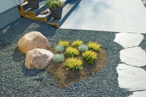 Isot liuskekivet on ladottu käytäväksi, jolla yhdistetään etupiha oleskelu pihaan. Liuskekivet on ladottu mustan soran tasoon ja ne myötäilevät graniittinupukivistä reunaa.