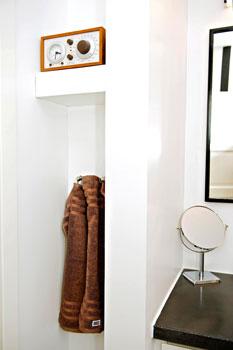 Seinäsyvennys kätkee sisäänsä kylpytakkien koukut ja musiikkilaitteita varten rakennetun hyllyn.