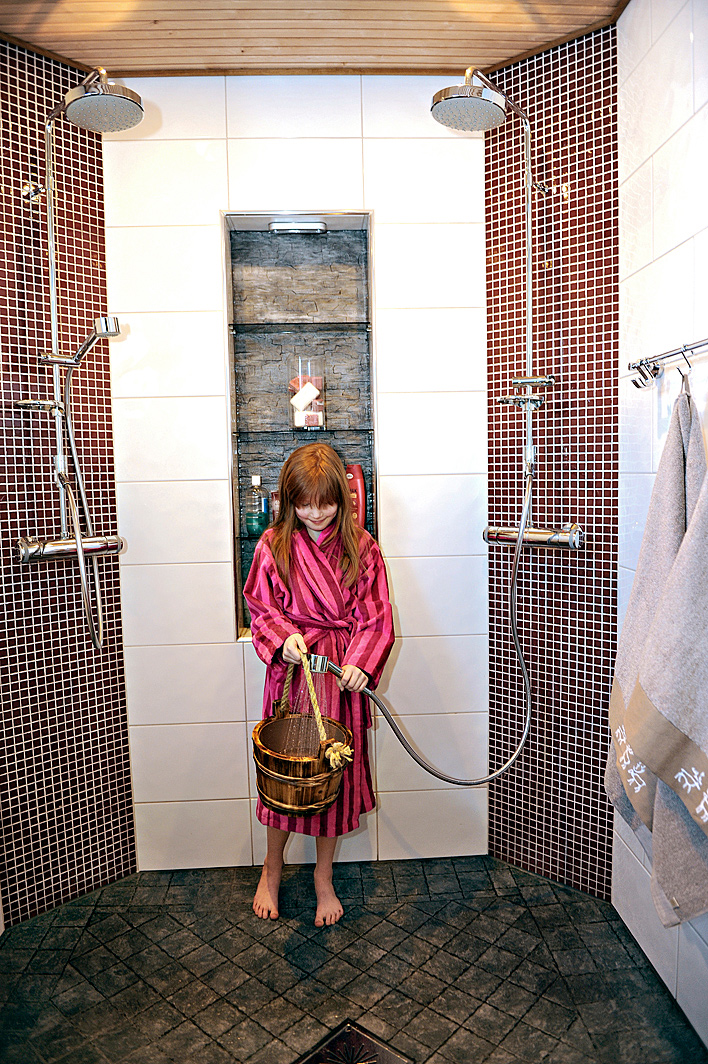 Punaiset mosaiikkilaatat tuovat väriä pesuhuoneeseen. Hyllysyvennys on käytännöllinen.