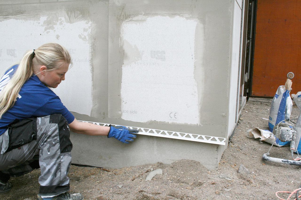 Seinän alareunasta saadaan siisti ja suora siihen tarkoitetun listan avulla. Lista painetaan tuoreeseen saumalaastiin kiinni lastan avulla. Kiinnitä lista kunnolla painamalla se voimakkaasti laastiin.