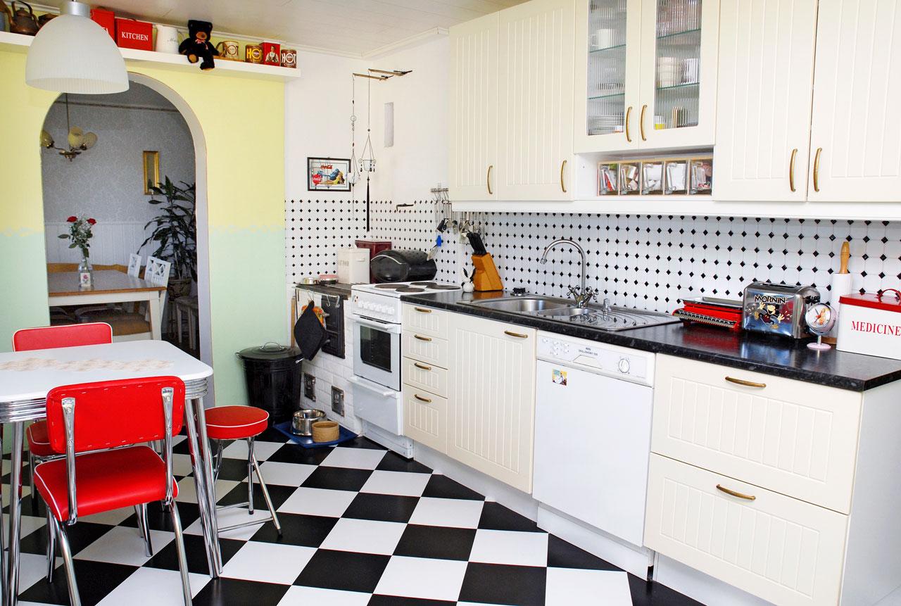 Mustavalkoinen laattalattia, välitilalaatoitus, mittojen mukaan teetetyt keittiökaapit ja iloiset värit ovat persoonallinen yhdistelmä.