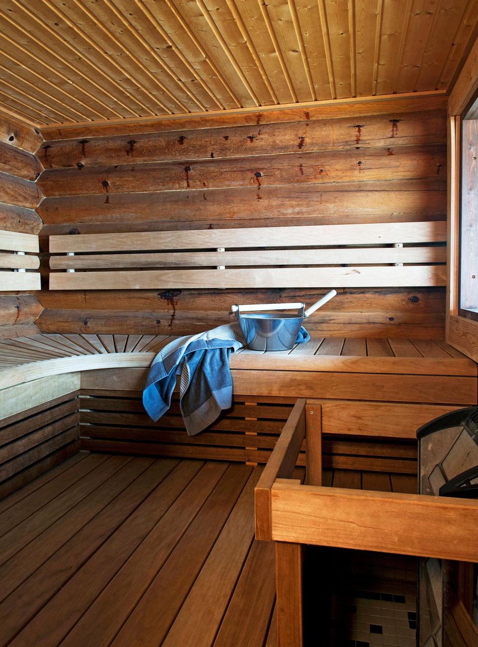 Saunan seinät ovat pyöröhirttä, mutta uusien lauteiden myötä rakennettuun selkänojaan on mukavampi nojailla kuin pihkaa puskevaan hirteen. Lauteilla bambua oleva Rento-kylpypyyhe. Lauteet ovat lämpökäsiteltyä haapaa, ja rakennettu paikoillaan.
