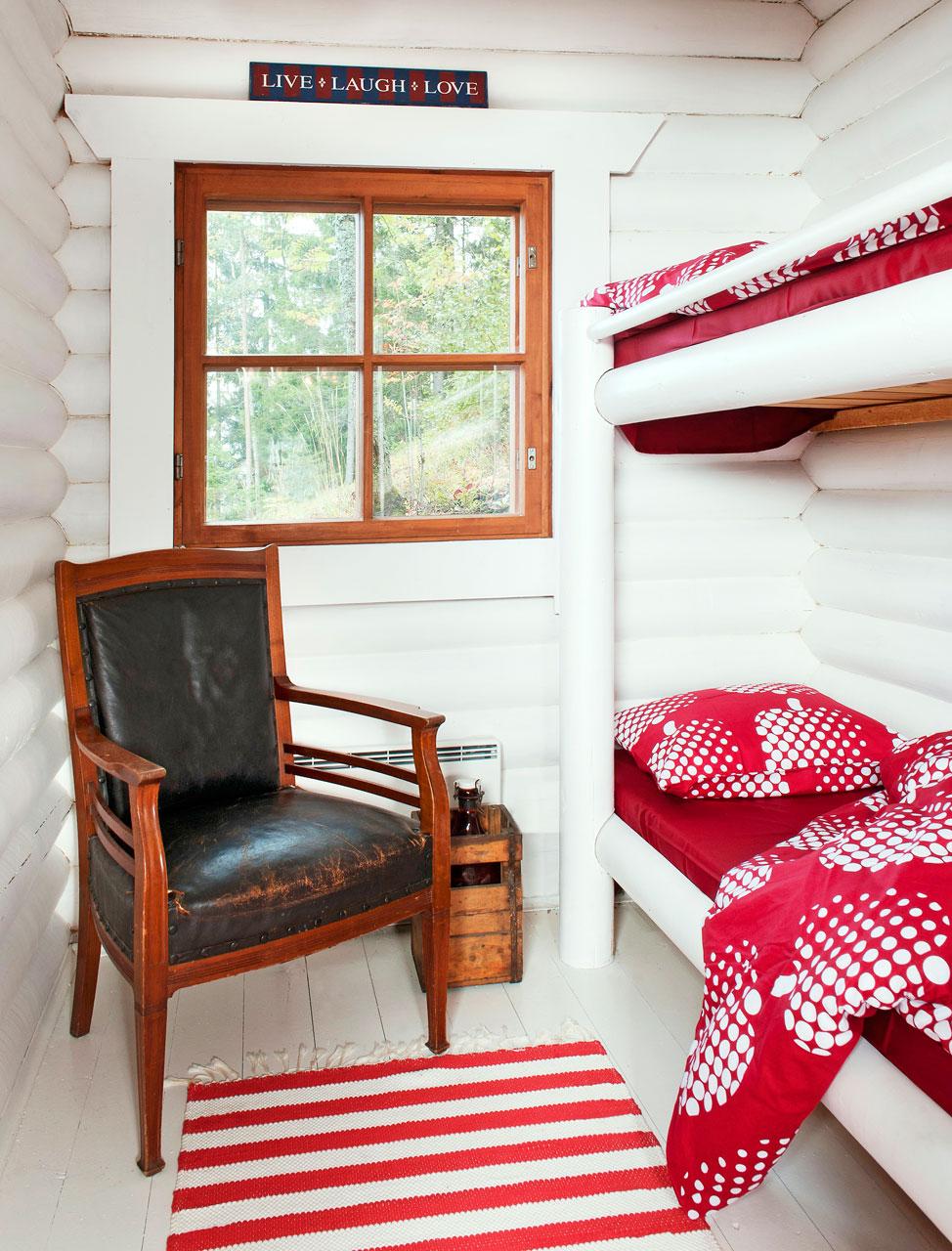 Hauska hirsisänky on kiinteä ja rakennettu kiinni seinään. Valkoinen väri sopii pyöröhirteen hyvin. Finlaysonin lakanat ovat nimeltään Optinen omena. Nurkassa oleva nahkatuoli on osa perintökalustoa, johon myös keittiön pöytä kuuluu.