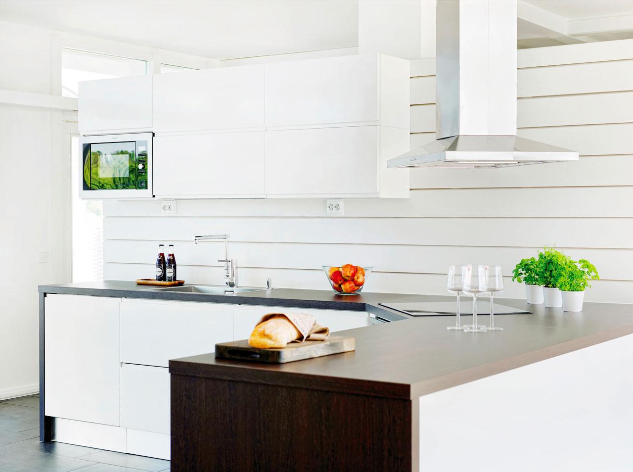 Modernia saaristolaistunnelmaa. Pelkistetyn minimalistinen ja selkeitä linjoja sisältävä keittiö tuo raikkaan vaikutelman. Säde-ovimalli on kiiltomaalattua mdf-levyä ja kehysmäisesti kulkevat tummat työtasot wenge-laminaattia. Kauniin yksinkertaisen keittiön viimeistelevät erikokoiset laatikko-osat, jotka on varusteltu sormiurilla.  Lisätietoja Topi-Keittiöt, www.topi-keittiot.fi