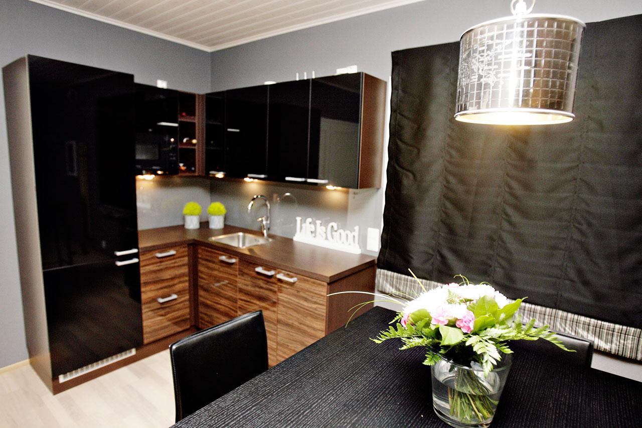 Tummasävyisen keittiönurkkauksen helmi on pystybaaritunnelmaa jäljittelevä pöytäryhmä.