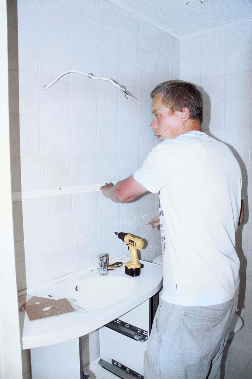 Otesan Oy:n Rami Koskinen asentamassa peilikaapin kiinnityslistaa.