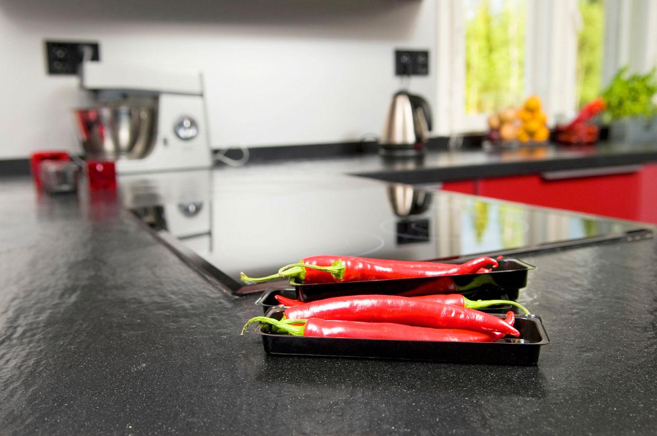 Keittiön mustaharmaat työtasot ovat kestävää, pestävää ja kolisematonta kvartsia.
