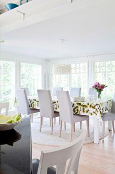 Ruokailutila tulvii valoa. Ruokapöydän italialaiset tuolit löytyivät Selkä- Linestä Lahdesta ja pyöreä villamatto on Ikeasta.