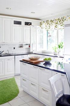VM-Carpetin pisaran muotoinen matto rikkoo sopivasti keittiön suorakulmaisuutta.