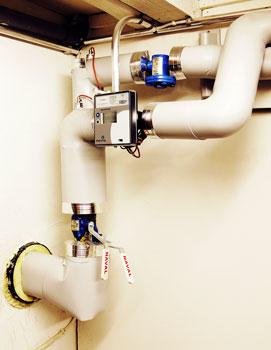 Lämmönjakokeskus liitetään seinän läpi tulevaan lämpöputkeen.