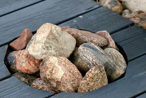 Oleskeluterassiin on sahattu reikä irtokiviä varten. Kivipesä koristaa lautapintaa.