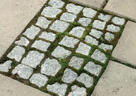 Pienin noppakivin ladottu alue tuo vaihtelua betonilaattojen tasaiseen pintaan.