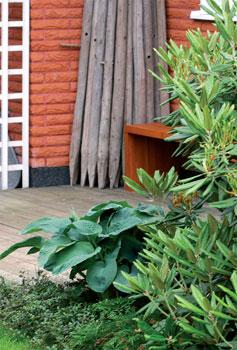 Suurten alppiruusujen talvisuojauksessa tukena käytettävät heinäseipäät saavat kesäisin olla esillä terassin nurkassa.