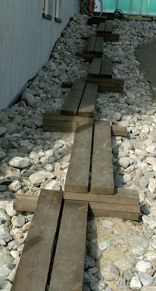Pitkospuita muistuttava lautapolku helpottaa liikkumista talon vierustan kivisessä rinteessä.