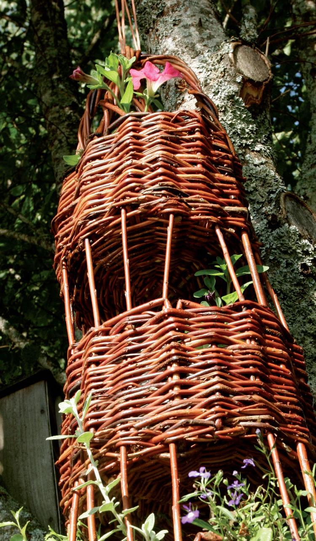 Puusta riippuva itse punottu kerrosamppeli sulautuu ympäristöönsä ja luo istutuspaikkoja ja runsaudentuntua.