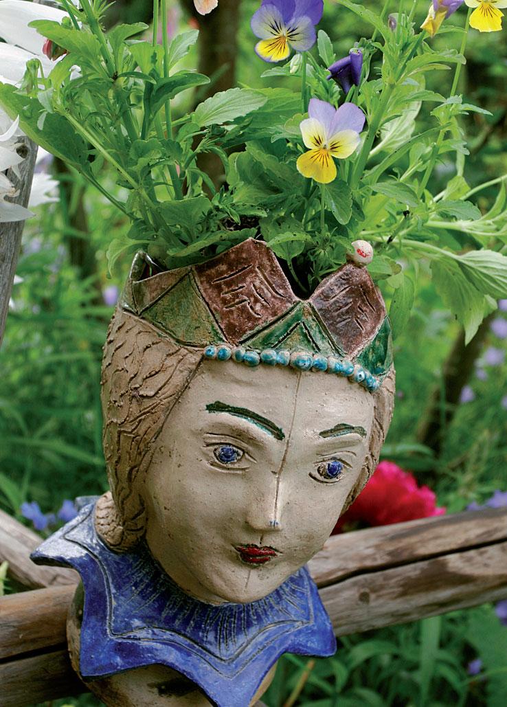 Nukenkasvoinen harlekiinihahmo toimii myös suloisena kukkaruukkuna orvokeille.