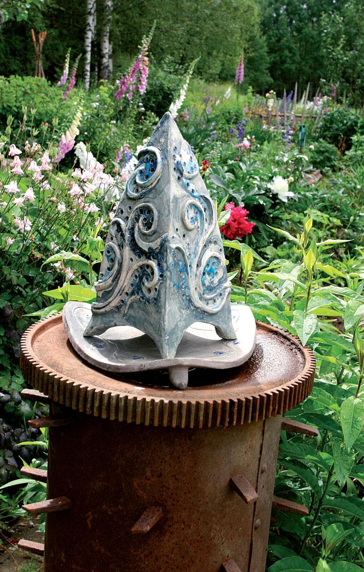 Savesta muotoiltu hiipan muotoinen kynttilälyhty koristaa puutarhaa. Esineen jalustana on vanhan puimakoneen osa.