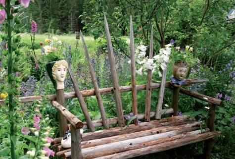 Heinäseipäistä tehty penkki sulautuu hyvin istutusten lomaan. Hovineito- ja harlekiini-hahmot pitävät penkille istuvalle seuraa.