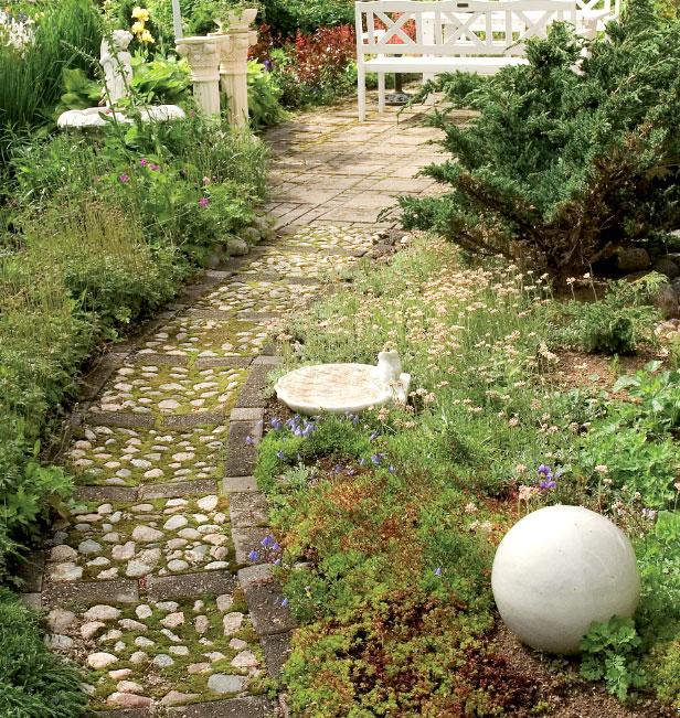 Talon itäpäädyn käytävä johtaa yhdelle monista oleskeluryhmistä. Kulkuväylien reunat ovat tiiviisti istutetut.