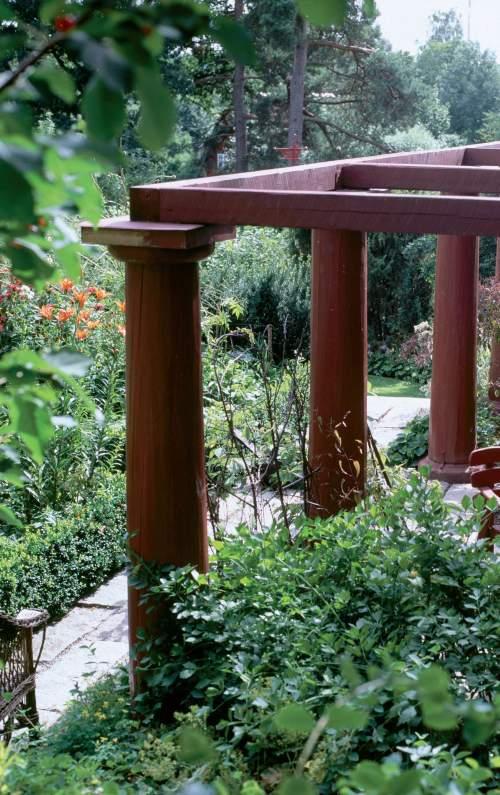 Kiinanpunaista pergolaa ympäröi rehevä puutarha. Jyhkeiden runkotolppien varaan perustettu komea rakenne ei kaipaa köynnöksiä.