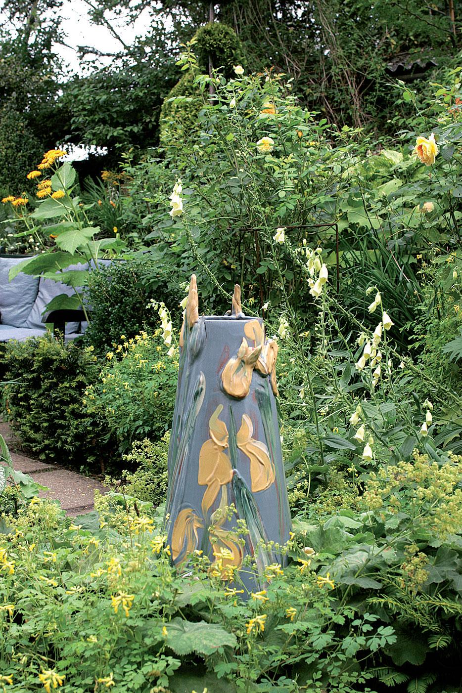 Keramiikkamaljakko pääsee oikeuksiinsa keltaisessa puutarhassa. Anne vie työnsä ammattikeraamikolle poltettaviksi. Jättipoimulehti (Alchemilla mollis) ja keltasormustinkukka (Digitalis grandiflora) ympäröivät teosta.