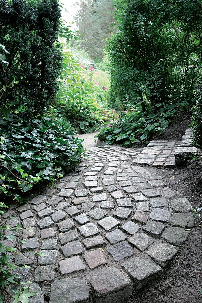 Noppakivistä ladottua käytävää reunustaa rehevä muratti (Hedera). Kiemurteleva käytävä on vastakohta puutarhan suoralinjaisille rakenteille.