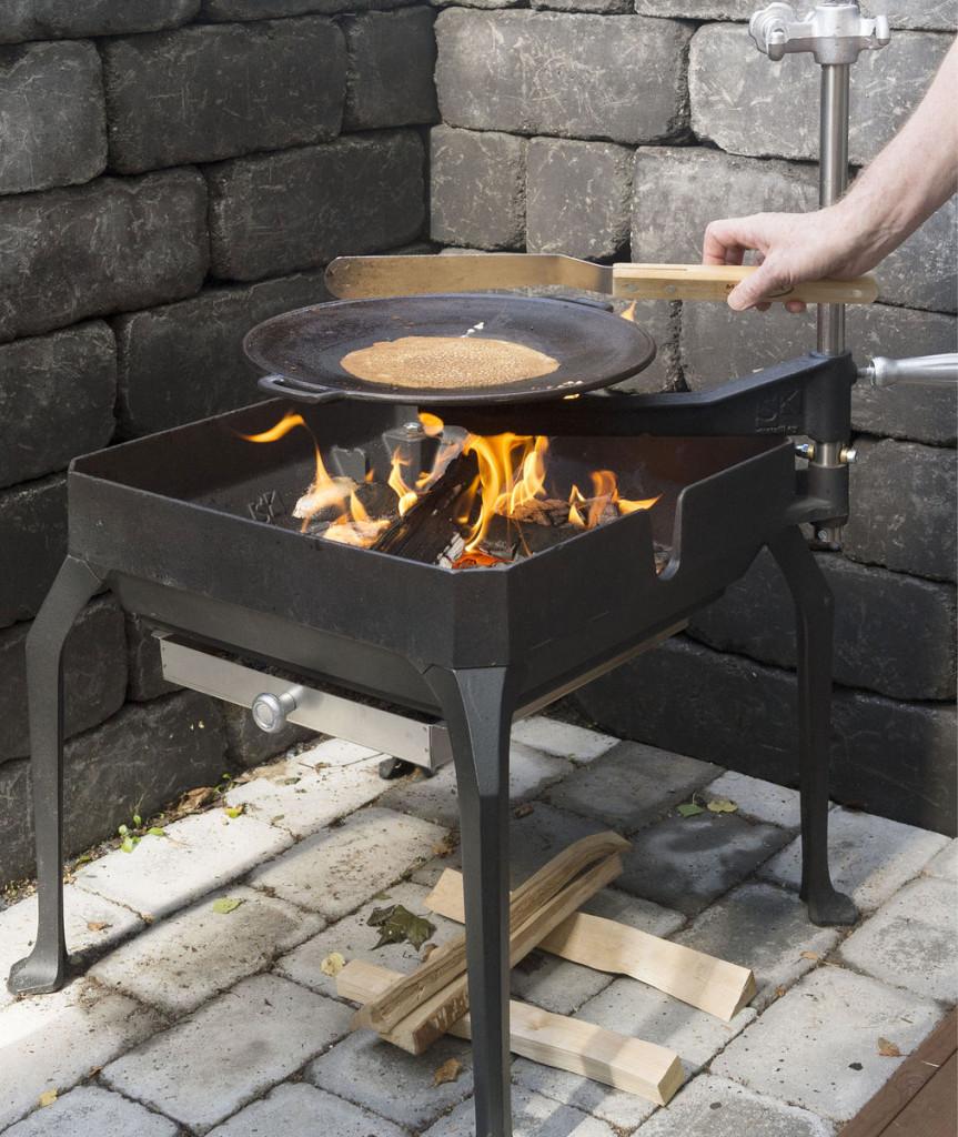 SK Metallin kesäkeittiö on täyttä rautaa, ja elävä tuli grilliä huomattavasti tun- nelmallisempi pienessäkin pihassa. Kokonaisuuteen kuuluu lettupannu, halsteri ja savustuslaatikko sekä haudutuspadan pidike ja koukku nokipannukahville. Lettupannu lämpiää tulella muutaman minuutin, jonka jälkeen voi käydä hommiin.