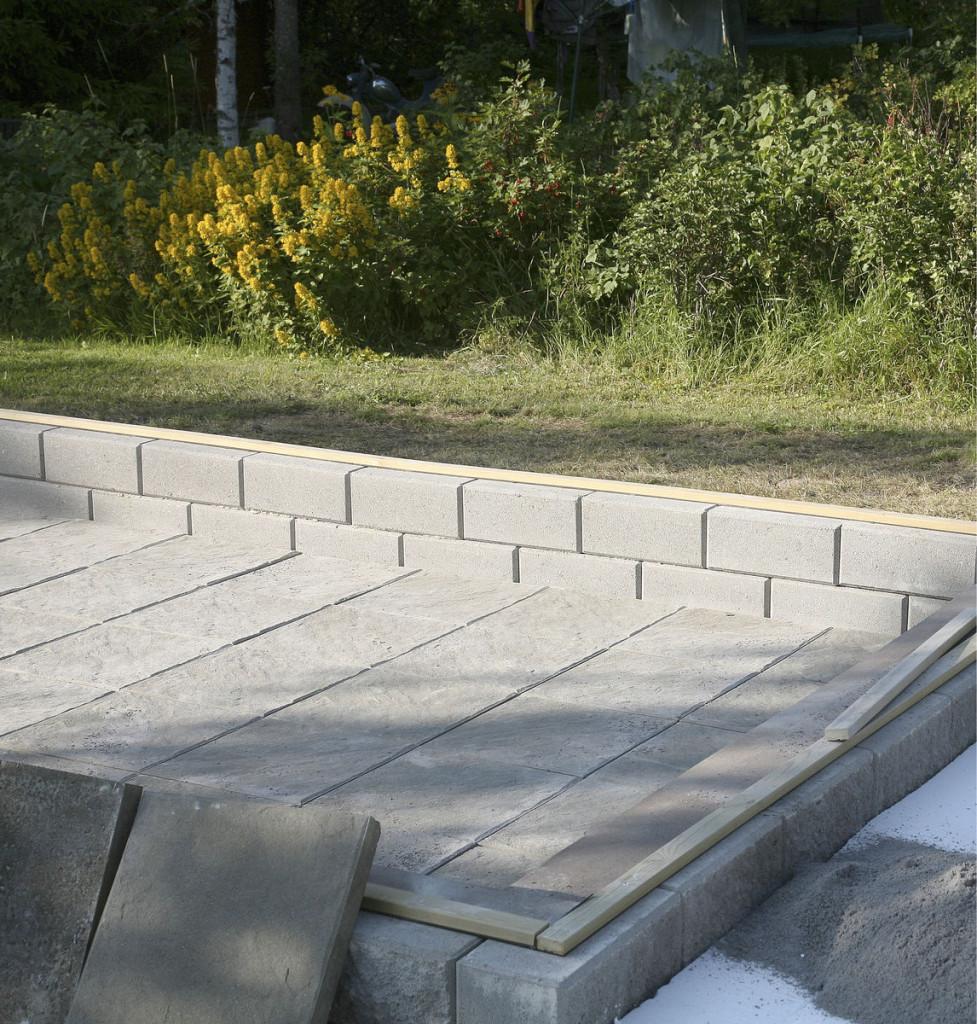Lattia ja lähiympäristö laatoitettiin Loimu-laatalla. Sokkelin yläpintaan liimattiin tervanauha estämään kosteuden siirtyminen kasvihuoneen rungon kiinni- tysalustana toimivaan kestopuuhun.