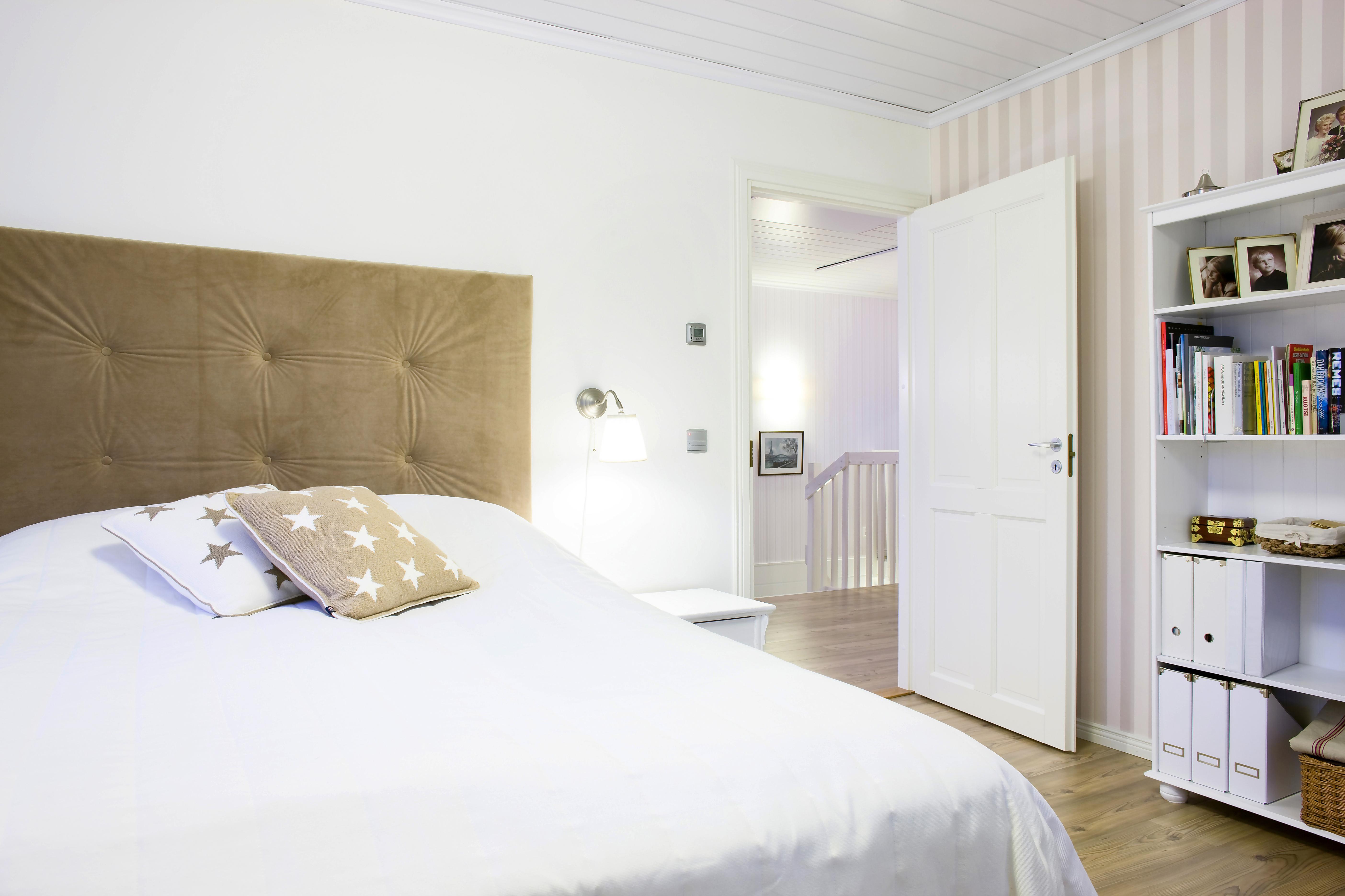 Makuuhuoneet, toinen wc ja kodinhoitohuone sijaitsevat yläkerrassa. Hiekanruskea ja valkoinen luovat rauhallisen tunnelman vanhempien makuuhuoneeseen. Sängynpääty on Riston tekemä.