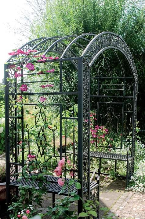 Rustiikkinen köynnöskaari houkuttelee puutarhaan. Ajan myötä metallinen portti istuimineen peittyy ruusujen ja kärhöjen alle.