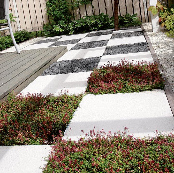 Valkoiseksi maalatut betonilaatat ja ajuruohomättäät muodostavat hauskan lattiapinnan.