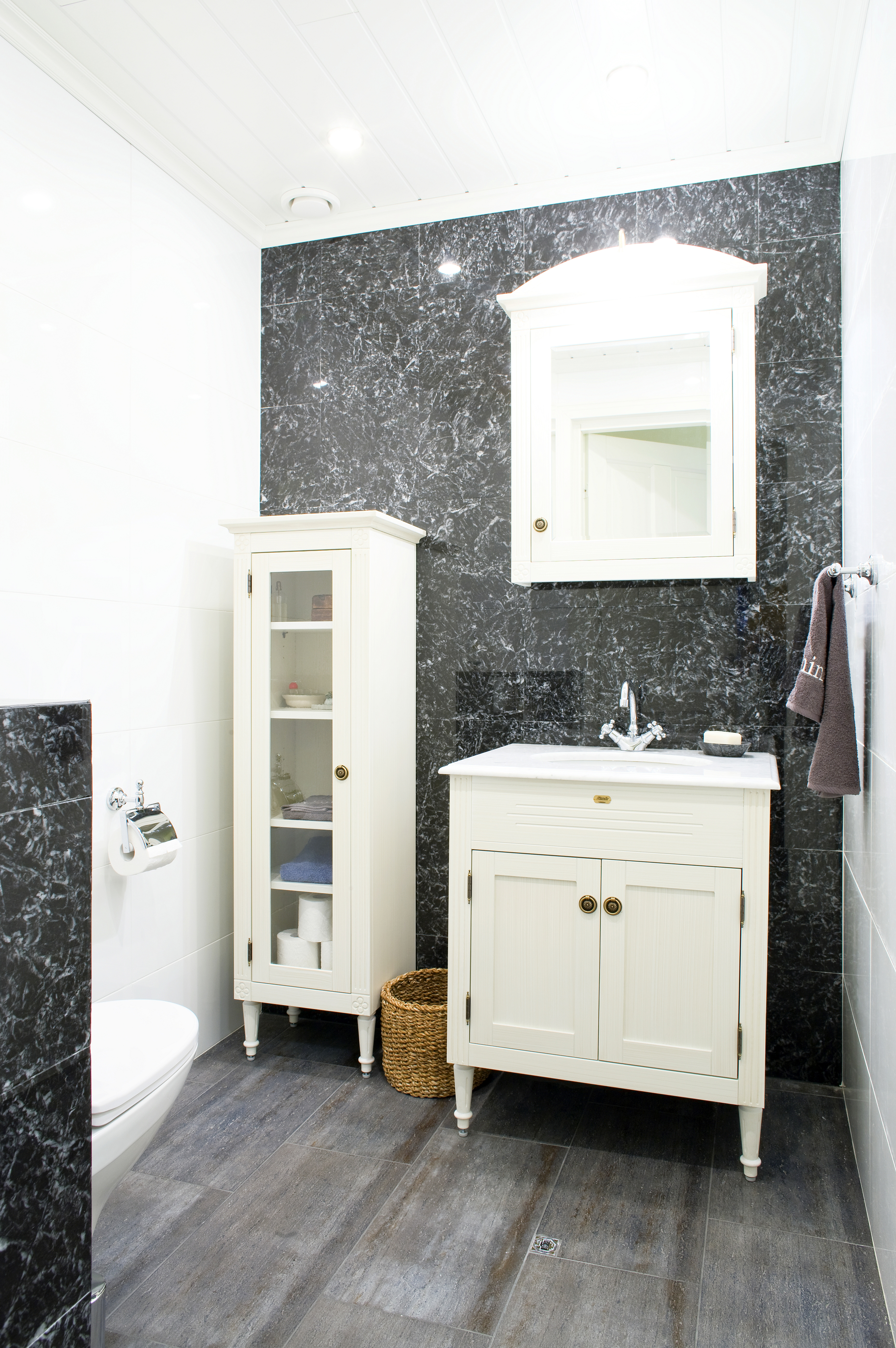 Kuninkaallista tyyliä alakerran wc-tiloihin tuovat Vedumin Louis-sarjan jyhkeät kalusteet. Seinät ovat mustaa marmoria. Talon kaikki laatat ovat Kaakeli Taikureiden mallistosta.