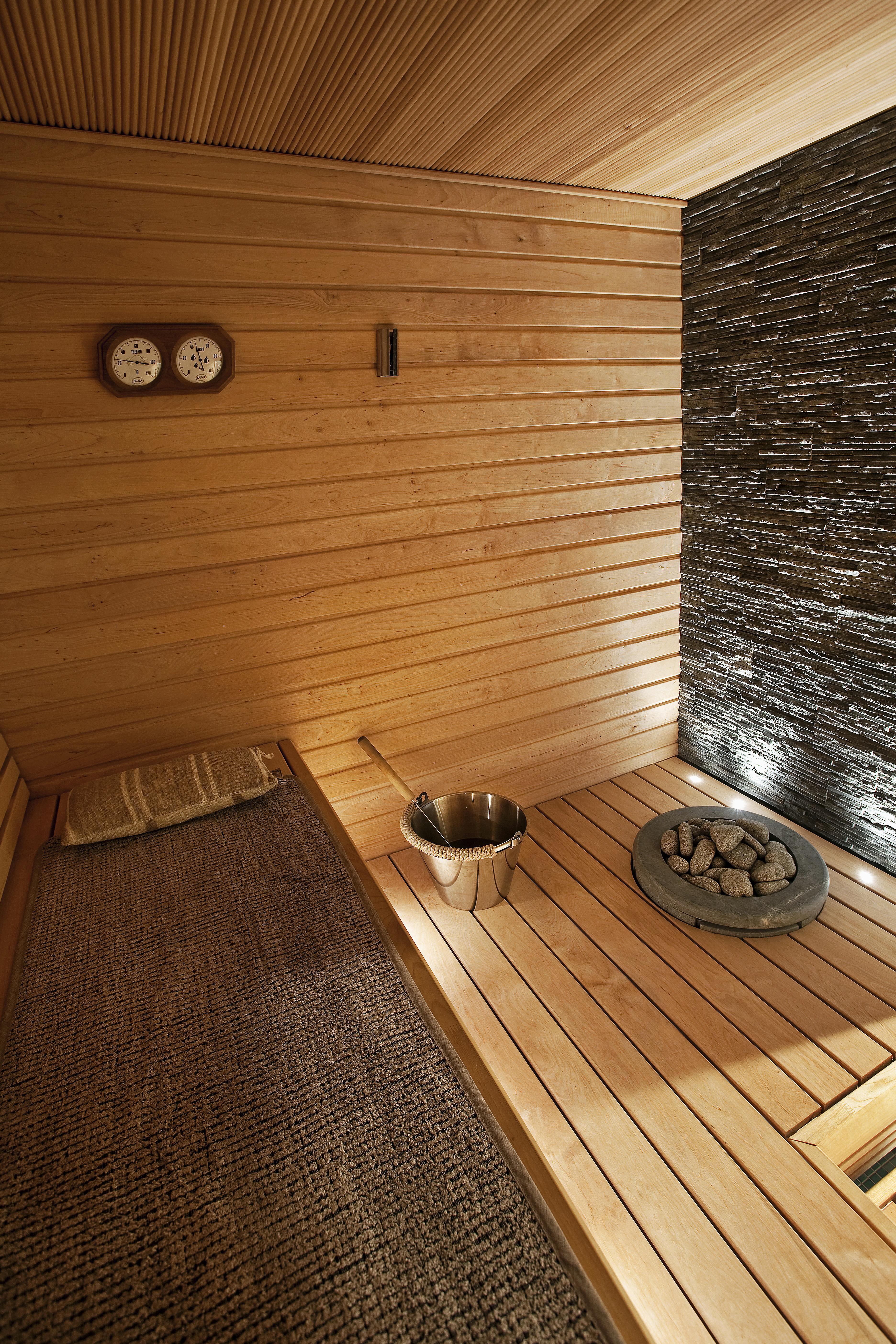Yksinkertaista. Vaalea puu, luonnonkivi ja hämyisä valaistus tekevät saunaan levollisen tunnelman. Alalauteeseen upotettu kiuas on Kastorin.