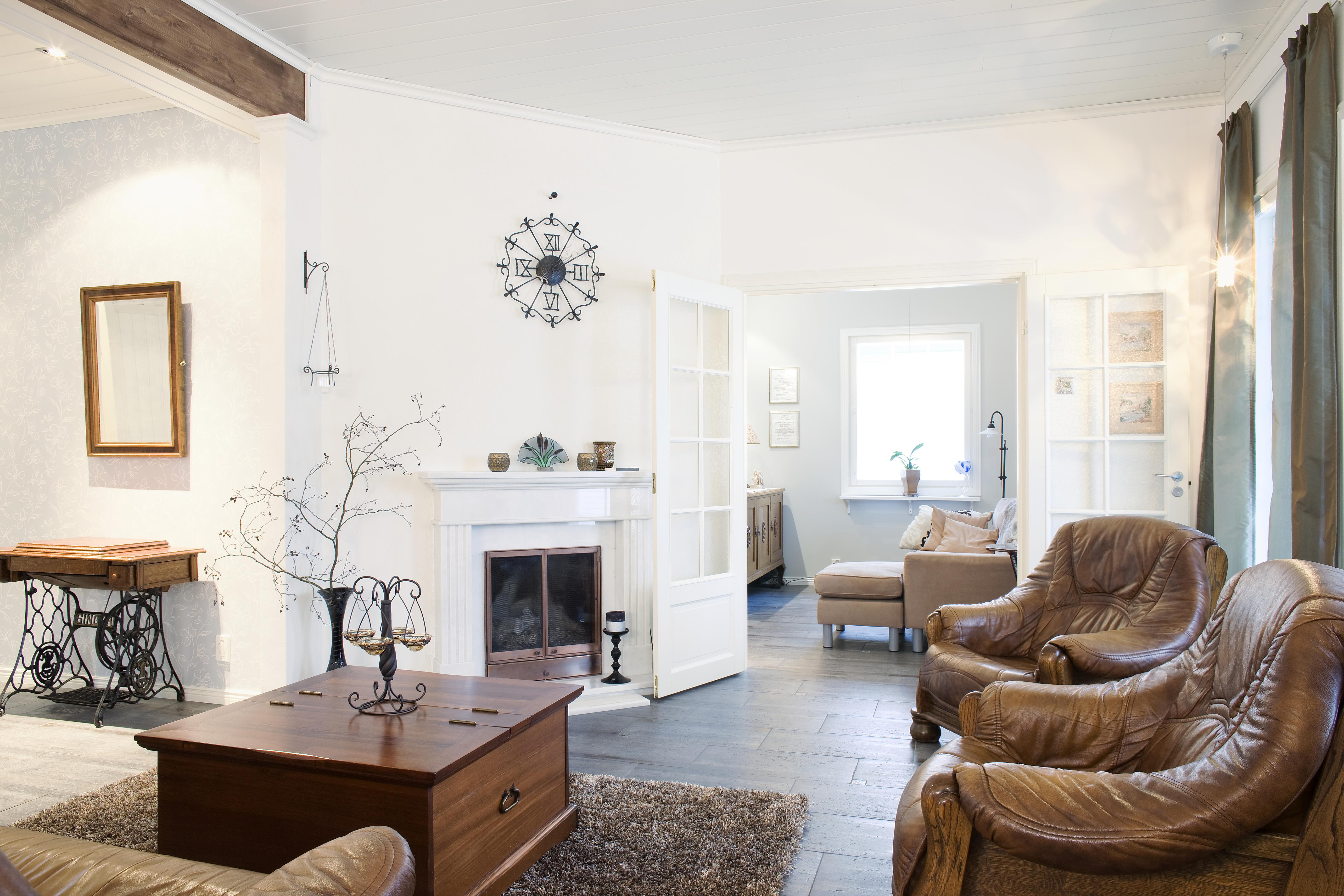 Marmorinen manttelitakka on kodikkaan olohuoneen keskipiste. Kaksoisovien takana on erillinen tv-huone. Kellon on tehnyt isäntä joskus koulupoikana.