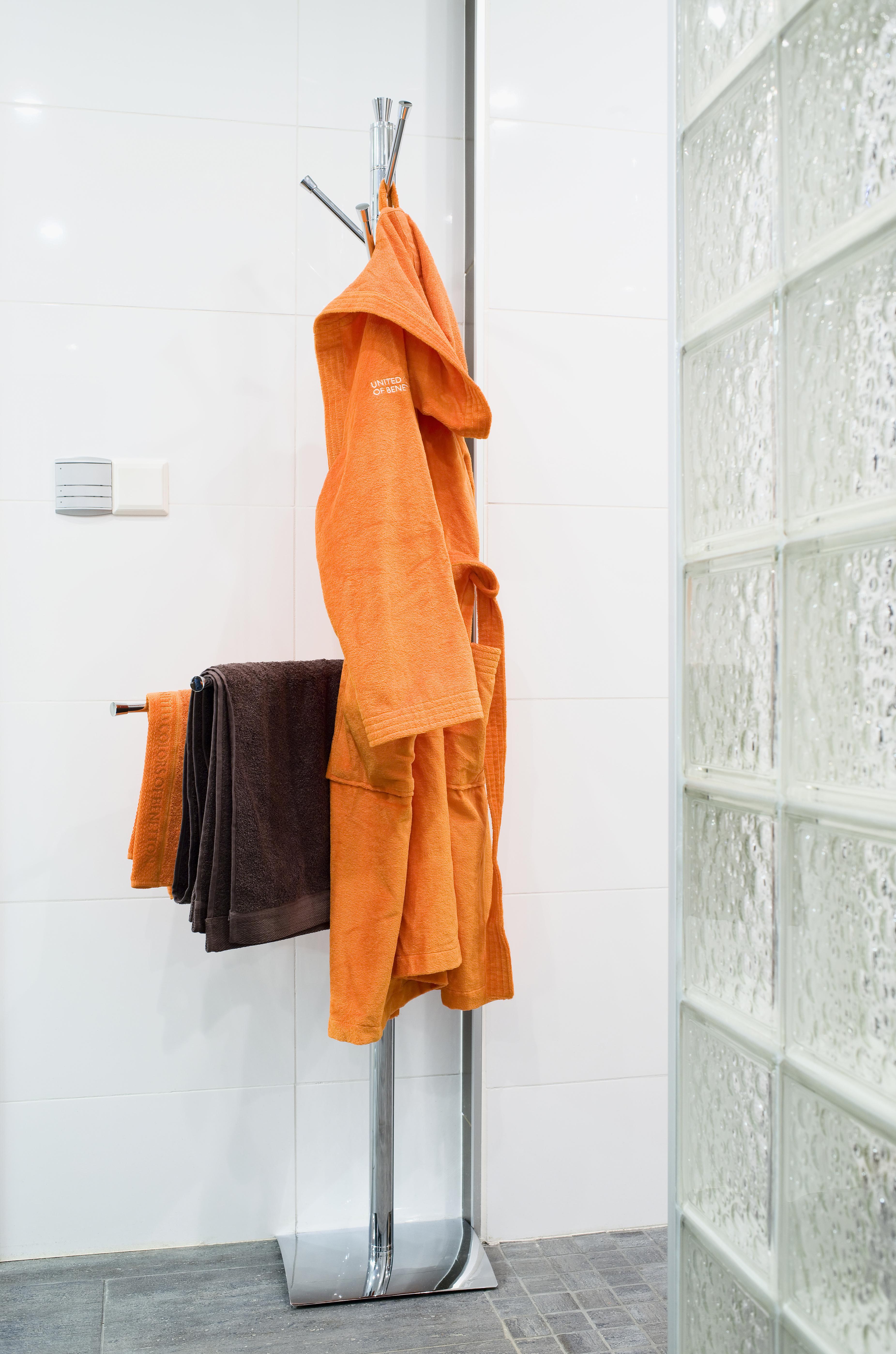 Kylpytakit ja pyyhkeet voi kätevästi ripustaa Wenkon telineeseen. Lasitiiliseinä erottaa suihkutilan muista peseytymis- ja pukeutumistiloista. Kuvausrekvisiitta Stockmann.
